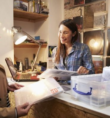 Female customer being served at the counter of a record shop